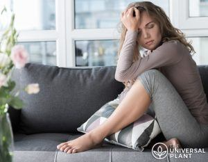 Woman with head in hand considering if there are cbd side effects